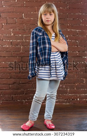 Girl 6 years old in jeans and shirt is thrown against the wall - stock photo