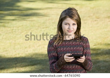 Girl (11 years) outdoors on grass holding camera