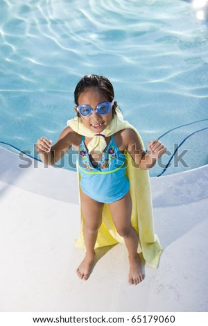 Girl, 7 years, playing by swimming pool in pretend superhero costume - stock photo