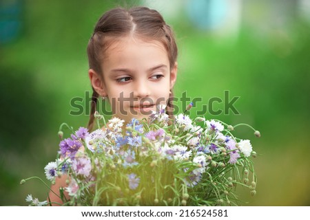 Girl 5-6 years with a bouquet of wildflowers. Portrait with small depth of field on green background. - stock photo