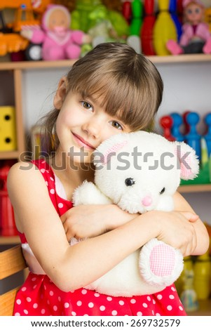 Girl 6 years with blond hair in a red dress with white polka dots sitting on a chair, holding a stuffed toy white bear - stock photo