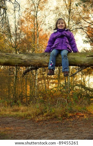 Girl (5yr) sitting on a tree in an autumn forest - stock photo