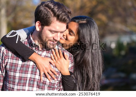 Girlfriend and boyfriend hugging and kissing outside - stock photo