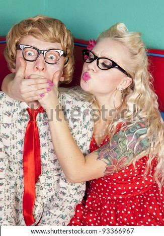 Girlfriend is trying to kiss a shy nerdy guy - stock photo