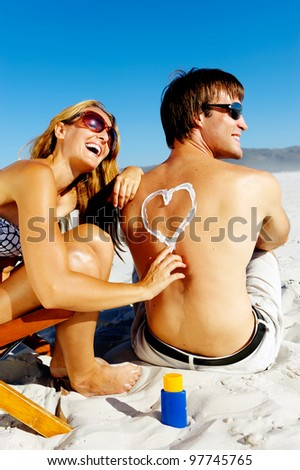 Girlfriend playfully draws a heart on her boyfriends back with spf suncream to protect him from the harsh sun while on their tropical summer beach vacation - stock photo