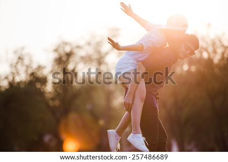 Girlfriend ride back of boyfriend. Couple relaxing in the garden at evening. Sunshine making warm and them happiness. - stock photo