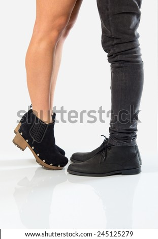 Girlfriend standing on her toes to reach and kiss her boyfriend - stock photo