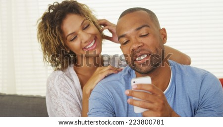 Girlfriend watching over boyfriend's shoulder as he texts - stock photo