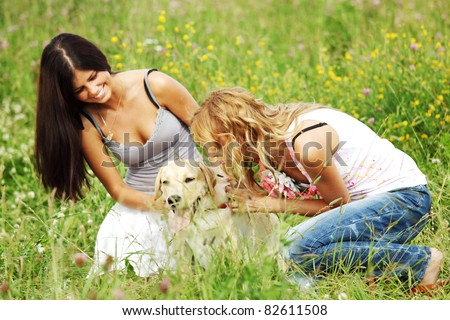 girlfriends and dog in green grass field - stock photo