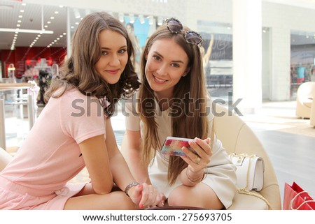 Girlfriends checkin an email in smartphone - stock photo