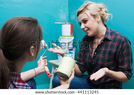 girlfriends discuss how best to paint the walls with paint