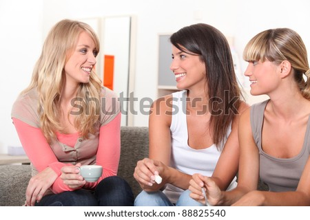 Girlfriends drinking  coffee on a sofa - stock photo
