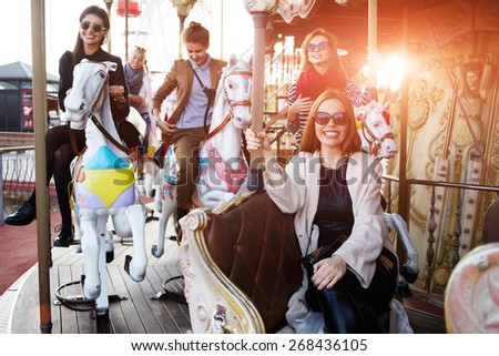Girlfriends enjoying time together while riding on a merry go round during vacation holidays, group of attractive women having fun riding on carousel in amusement park - stock photo