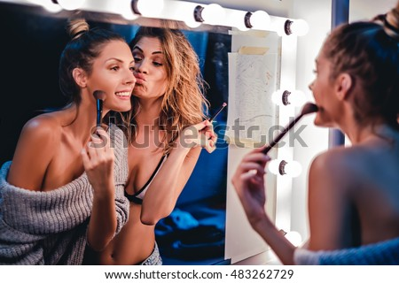 Girlfriends fooling around in front of a mirror while putting on makeup