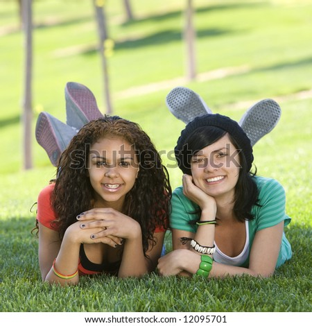 Girlfriends hang out in grass - stock photo
