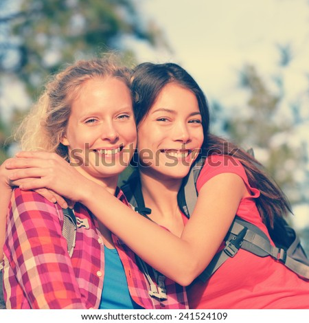 Girlfriends. Happy girls young women hiking portrait of smiling multiracial friends having fun together on hike in forest enjoying active healthy outdoors lifestyle. Asian and Caucasian woman outside. - stock photo