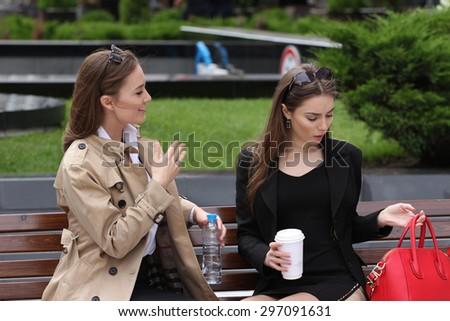 Girlfriends having fun on bench outdoors - stock photo