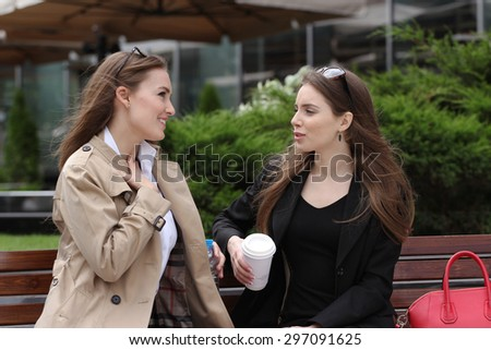 Girlfriends having fun on bench outdoors daytime - stock photo