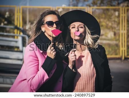 Girlfriends holding fake pink lips - stock photo