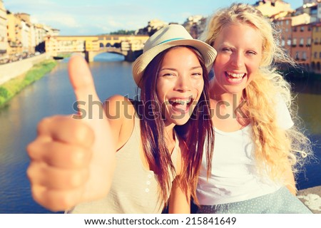 Girlfriends in city happy giving thumbs up.  - stock photo