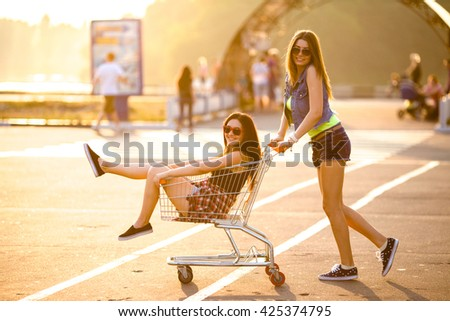 Girlfriends laughing. Girlfriends ride in a cart at the supermarket on the streets of the city. - stock photo