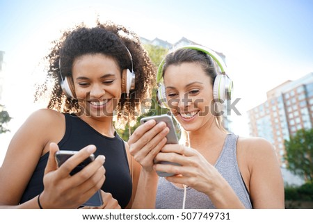 Girlfriends listening to music with smartphone while exercising