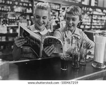 Girlfriends looking at magazine at soda fountain - stock photo
