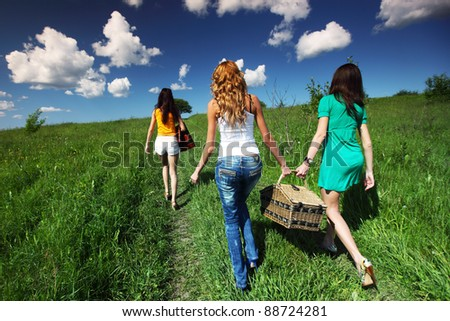 girlfriends on picnic in green grass field - stock photo