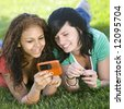 Girlfriends share a cell phone - stock photo