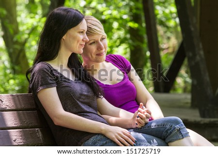Girlfriends sitting on park bench, horizontal