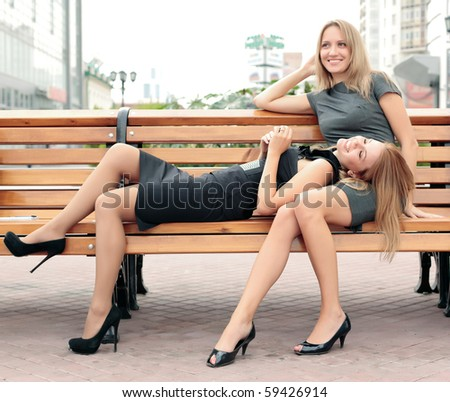 girlfriends smiling and laughing at city park - stock photo