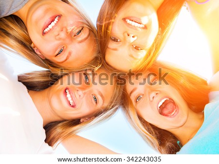 Girlfriends staying together, looking at camera and laughing over blue sky. Group of Four Teenage Girls having fun outdoors. Friendship concept. Group of smiling Joyful girlfriends making a huddle - stock photo