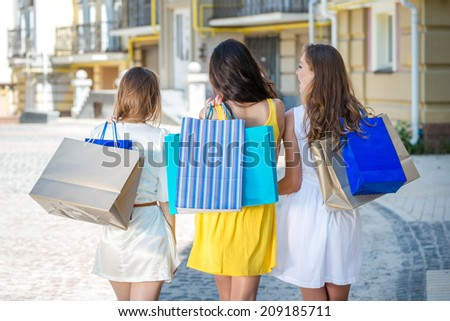 Girlfriends Walk to the store. Three girls holding shopping bags and walk around the shops. Smiling girlfriends having fun together walking on the street - stock photo