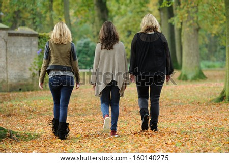 Girlfriends walking in forest during autumn - stock photo