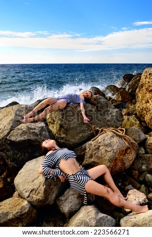 Girls after a shipwreck sitting on the rocks - stock photo