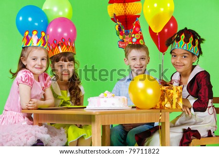Girls and boy in party hats and crowns sit at the table - stock photo