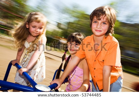 Girls and boy on carousel - stock photo