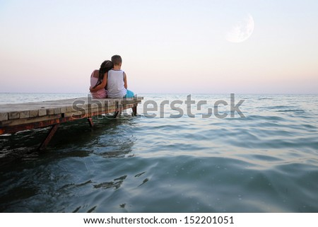 Girls and boys hugging at sunset on wooden jetty