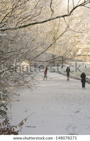 girls and boys on ice skates on a frozen canal in winter time with sunshine - stock photo