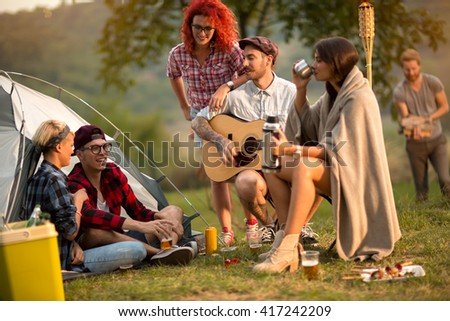Girls and guys socializing on sunset in camp in nature