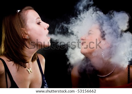 Girls and smoke. Isolated on black. - stock photo