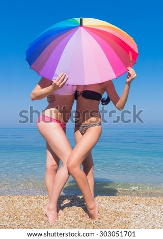 Girls at the sea. Two young women hiding under the iridescent parasol