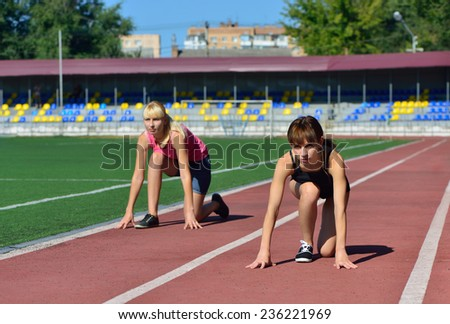 Girls athletics stadium. Preparing to run - stock photo