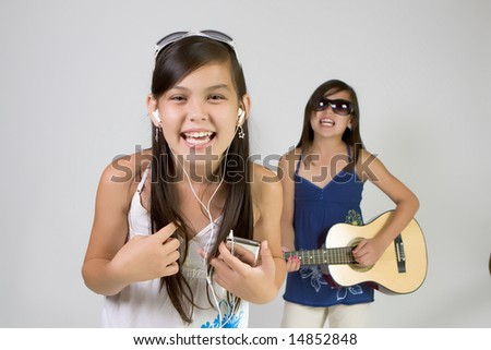 Girls band singing and playing on guitar - stock photo