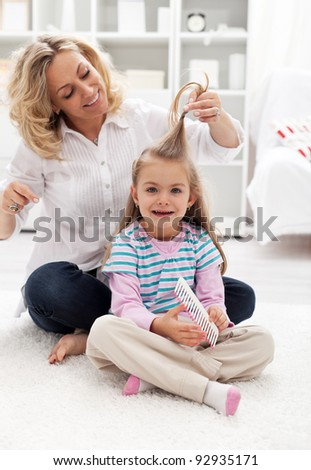 Girls beauty ritual - woman and child combing hair at home - stock photo