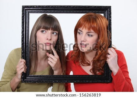 girls behind a wooden frame - stock photo