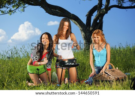 girls burn sausages on barbecue - stock photo