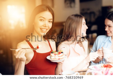 Girls celebrate the holiday on March 8 in a cafe. They are friends. Girls have tulips and gifts. They are cheerful and happy on a women's day.