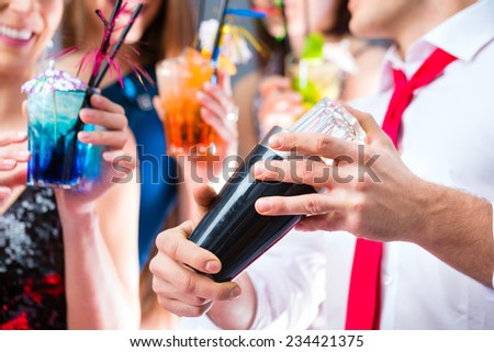 Girls celebrating with barkeeper in cocktail bar - stock photo