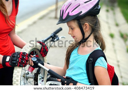 Girls children cycling Family pump up bicycle tire. - stock photo